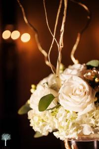 Tall vases filled with gold curly willow, topped with roses, hydrangea, hypericum berries and eucalyptus leaves with small curly willow branches
